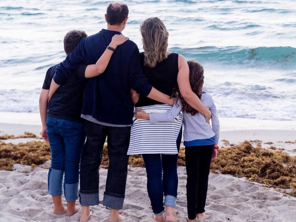 Family of four on the beach, looking out to sea